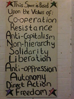 Handpainted sign that says: This space is based upon the values of Co-operation, Resistance, Anti-Capitalism, Non-hierarchy, Solidarity, Liberation, Anti-oppression, Autonomy, Direct Action, Freedom.